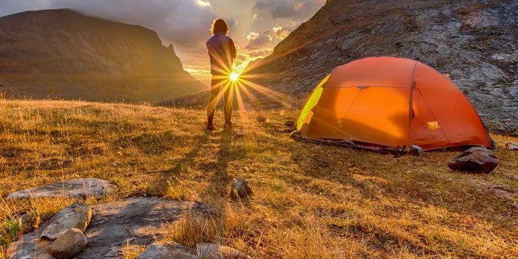 Person beside tent watching the sunrise in a mountain landscape.