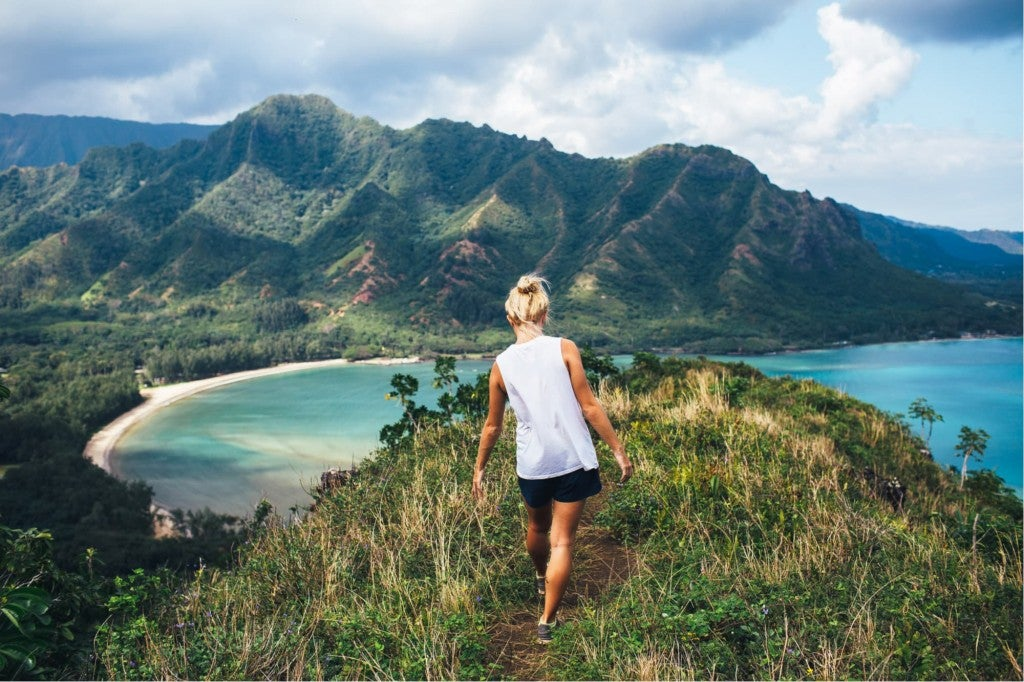 a woman on a cliff trail in hawaii hiking in oahu