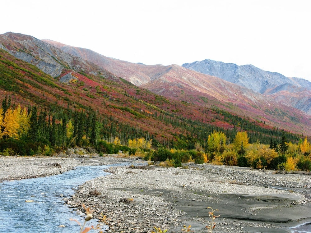 the brooks mountain range in alaska with a river running through