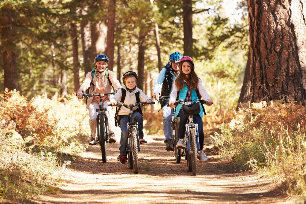 two kids and grandparents riding bikes along a trail