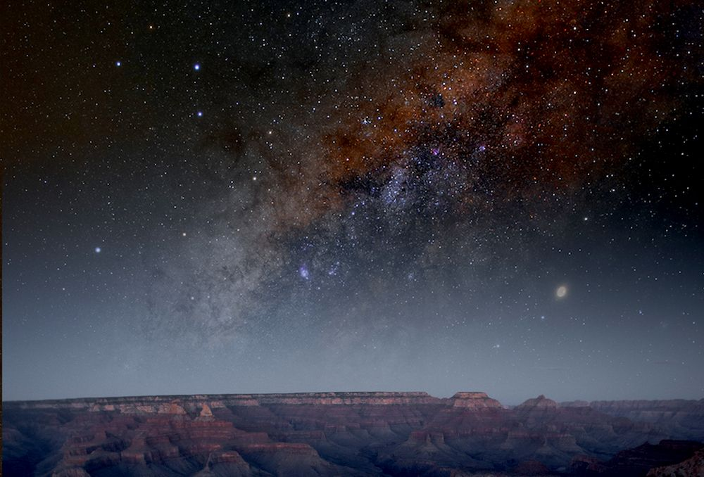 wide angle of the grand canyon at night displaying warm-toned galaxy in the sky above