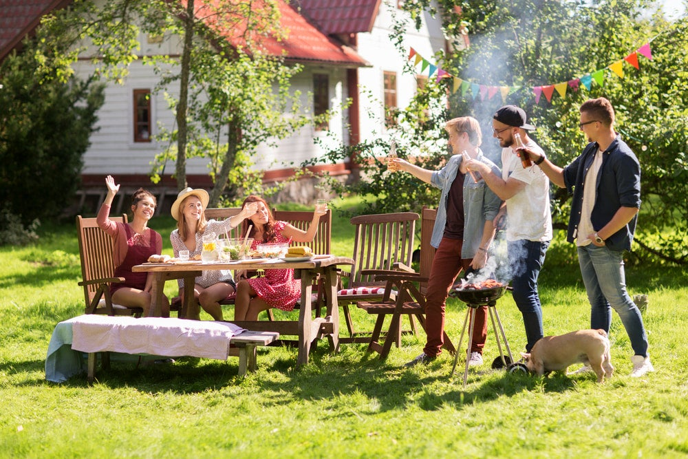 Group of friends having a BBQ in backyard