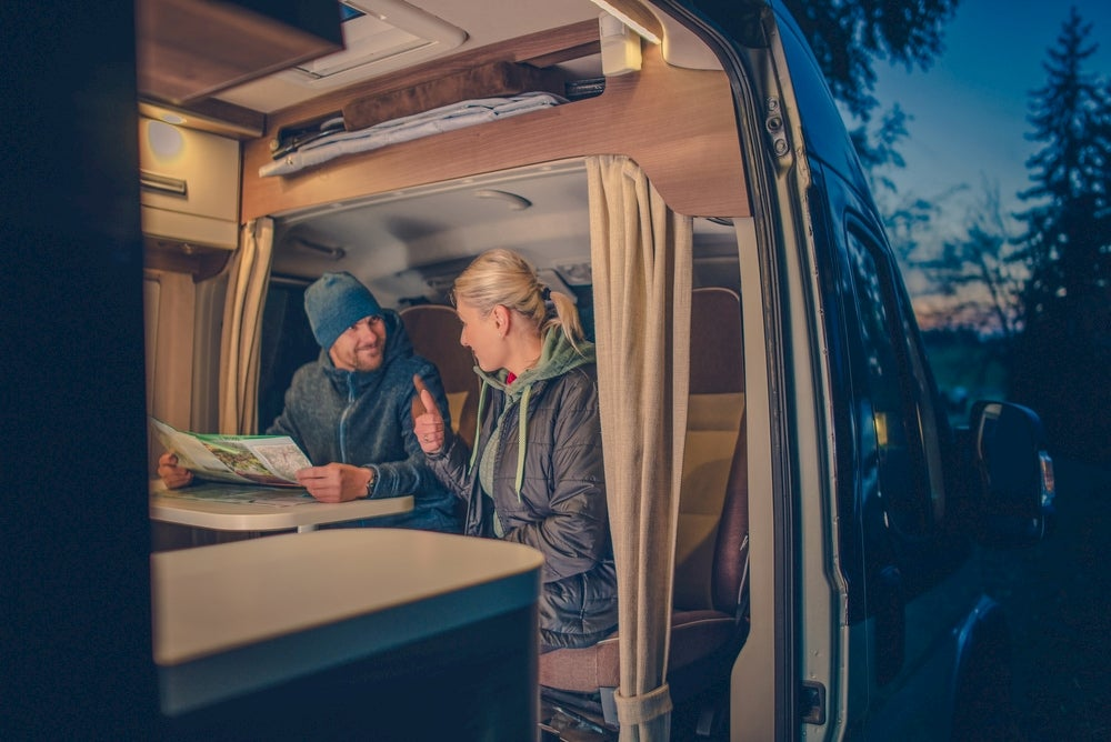Two people in RV looking at a map