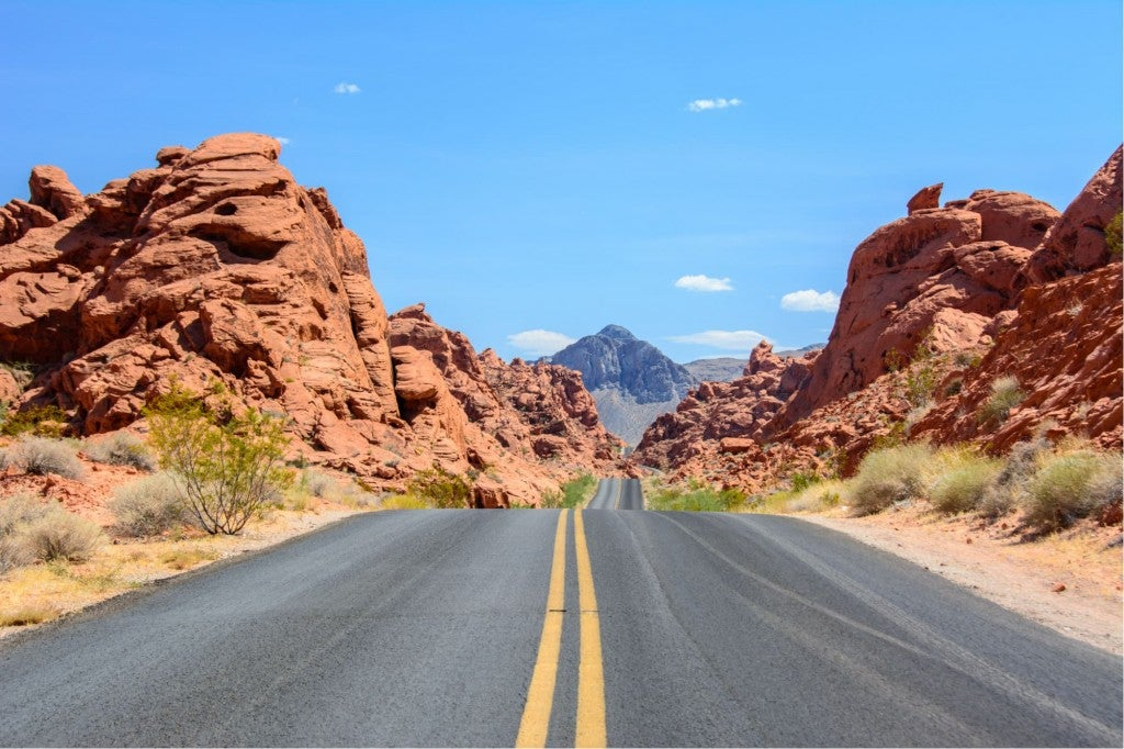 a highway traveling between red rock canyons in nevada