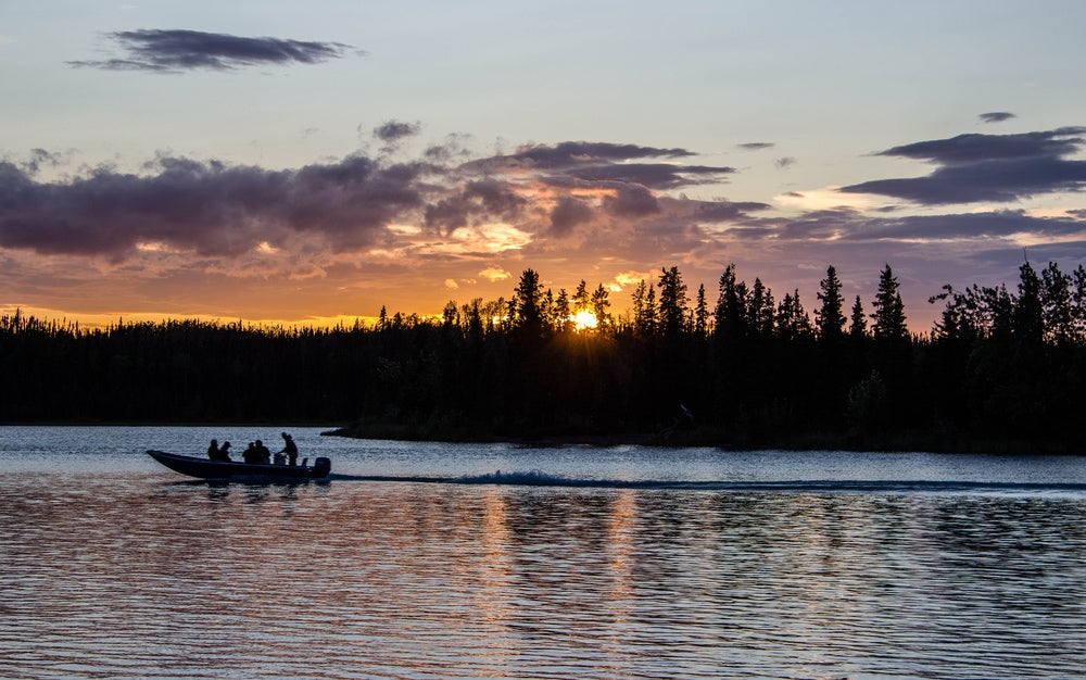a boat of three men fishing at sunset on the kenai river in alaska
