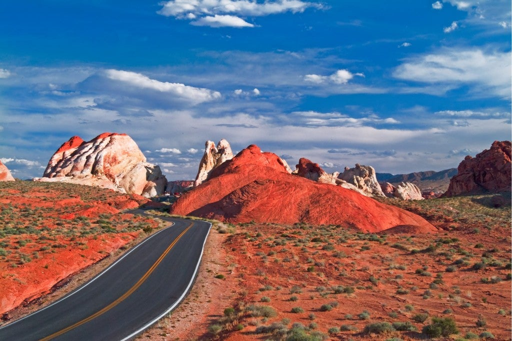 a road going through bright red desert rocks invalley of fire state park in nevada