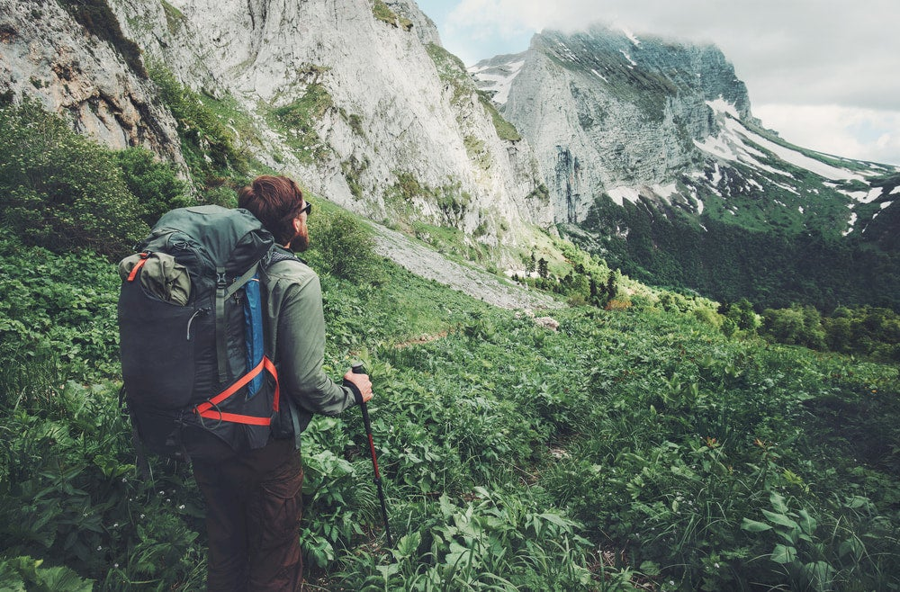 Man looking at mountains wearing backpack