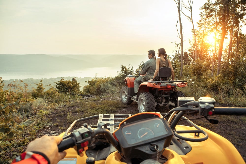 ATV riders looking out over a coast.