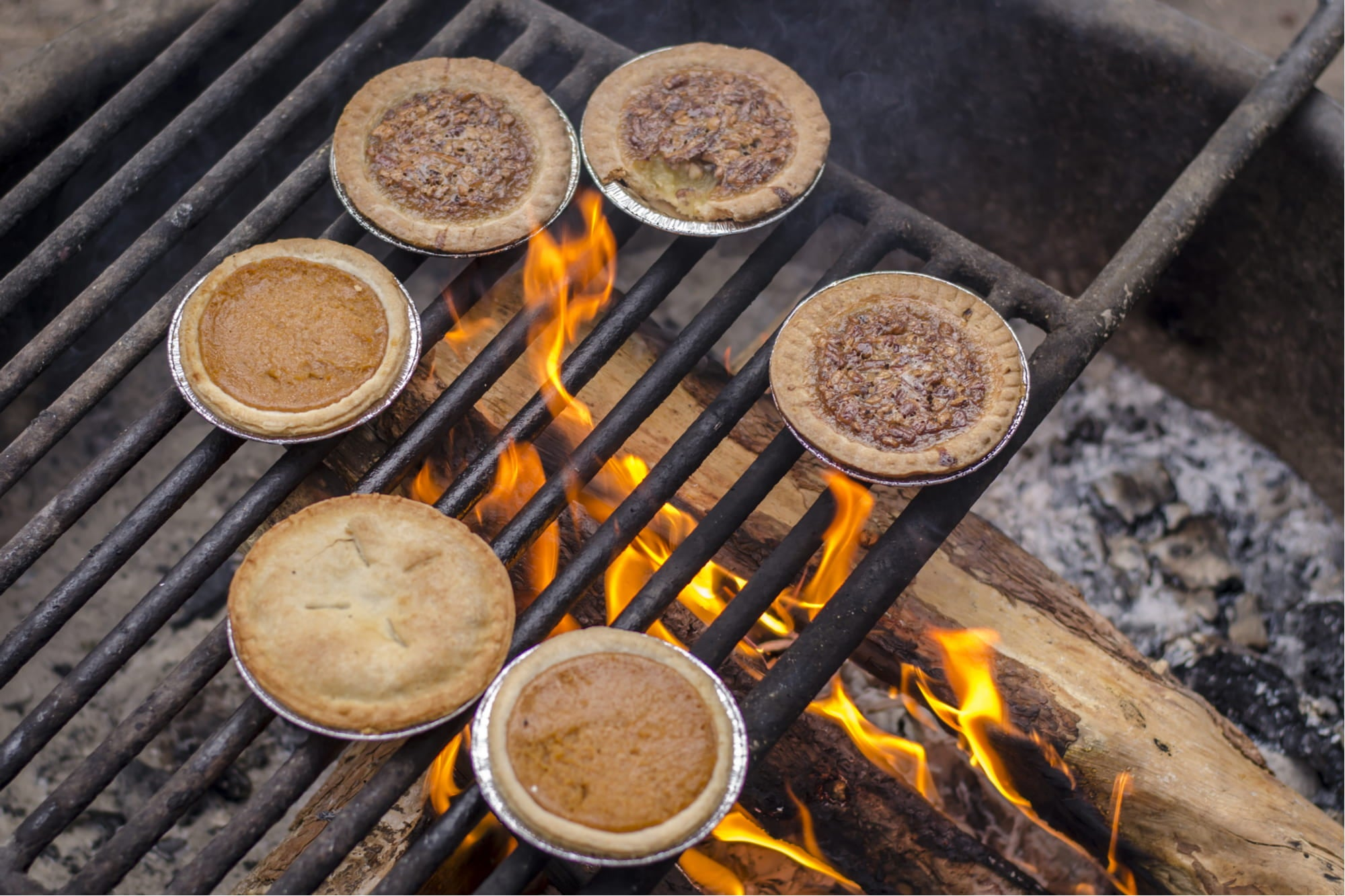 five pies on a grill over a campfire