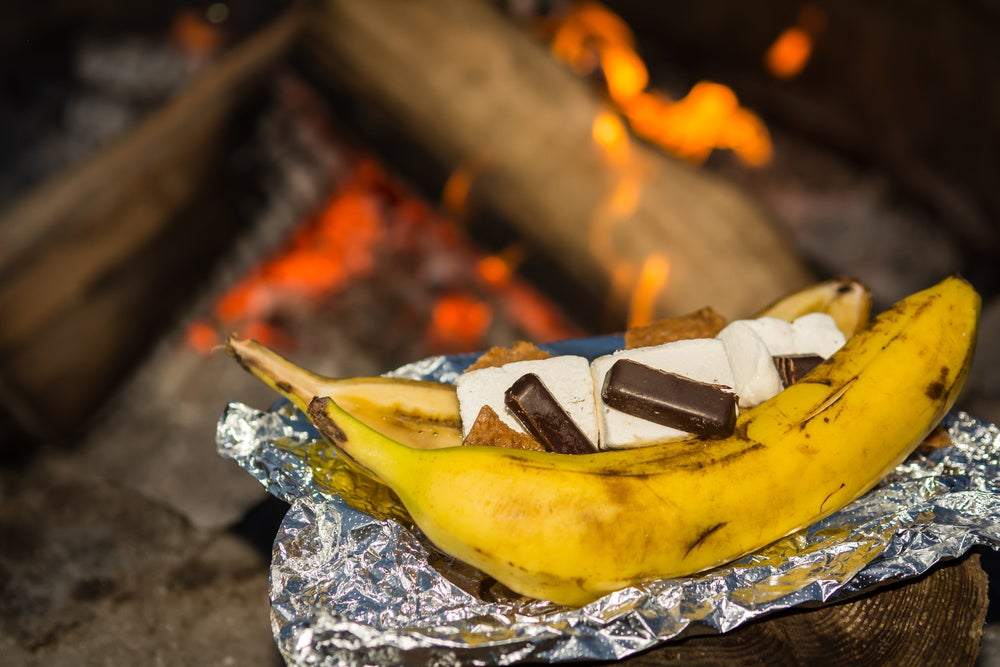 a stuffed banana on a campfire in tin foil