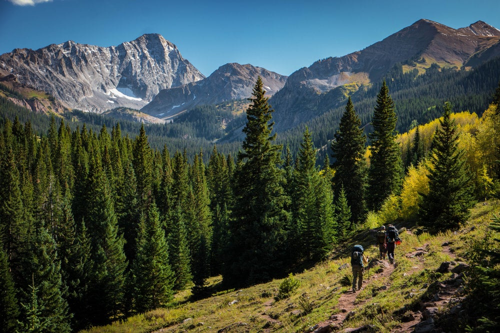 two hikers climbing capitol peak in colorado