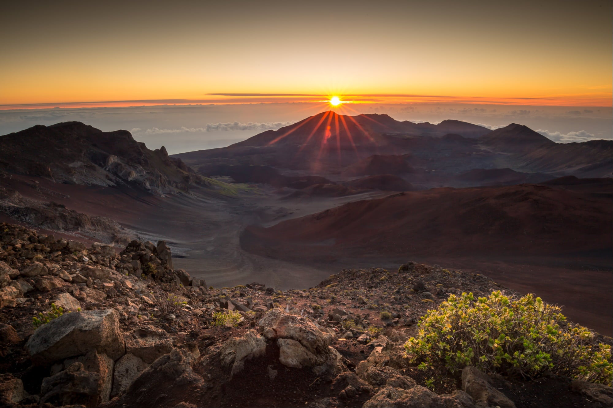 a sunset in haleakala national park lowering over a mountain