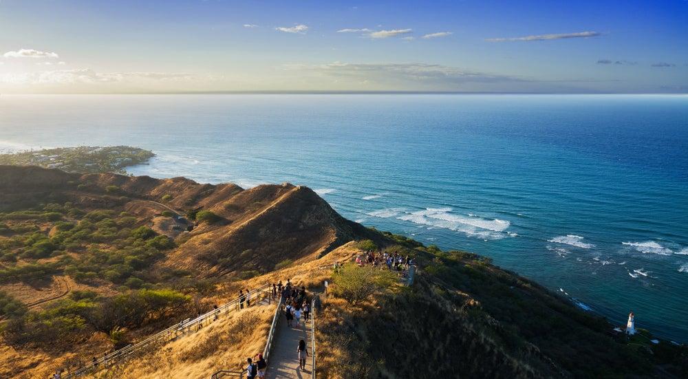 crowds of hikers walk up diamond head volcanic monument near honolulu, hawaii