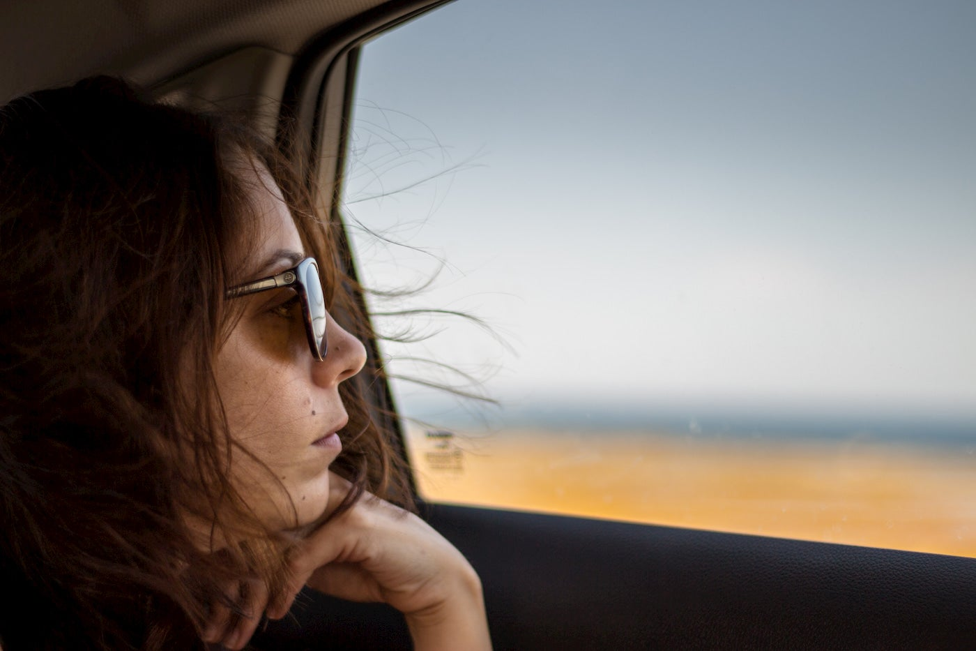 Women wearing sunglasses while looking out the window.
