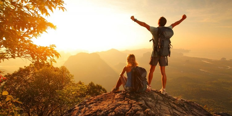 two people on the edge of a cliff at sunset