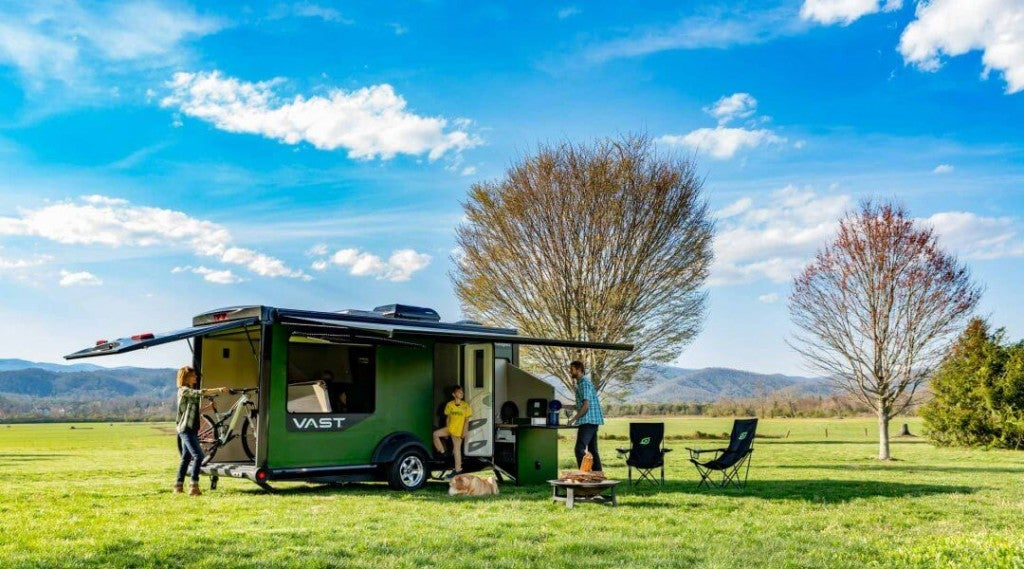 campers gather around sylvan sports modular camper in a field on a clear day