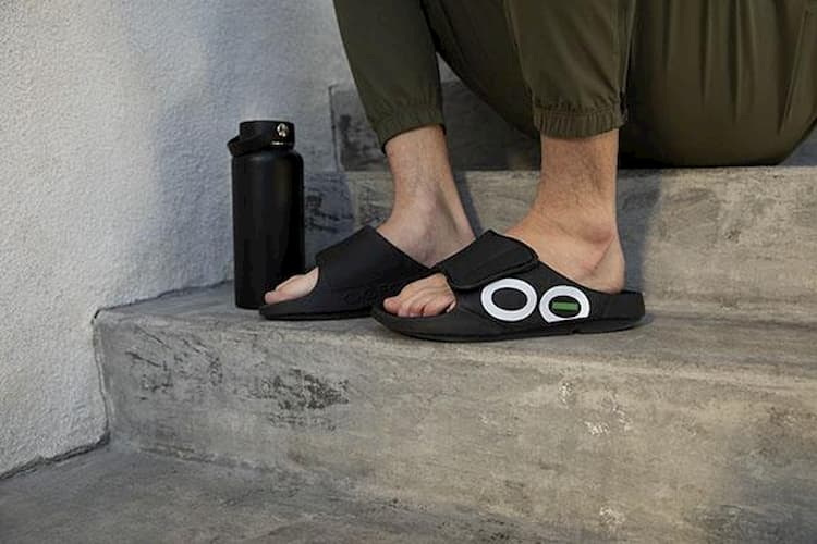 a man standing on a stair wearing oofos sandals