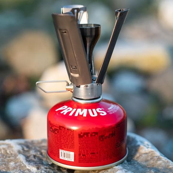 sleek primus firestick backpacking stove on a red can of fuel sitting on a rock