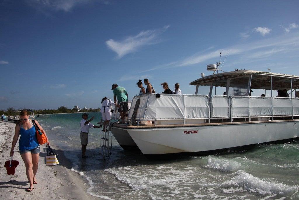 a group of people climb off a ferry onto cayo costa