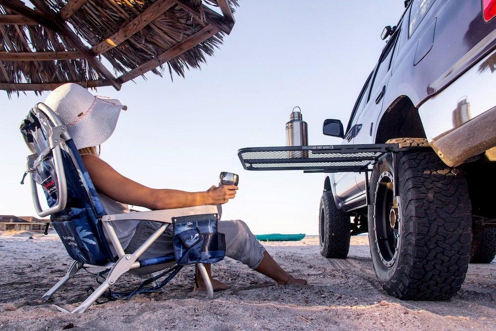a woman sitting on the beach near a tire table and a car