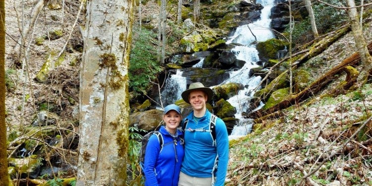 Two people posing with waterfall and trees behind them