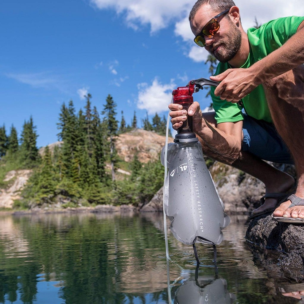 a man holding a water filter while filling it into a pack