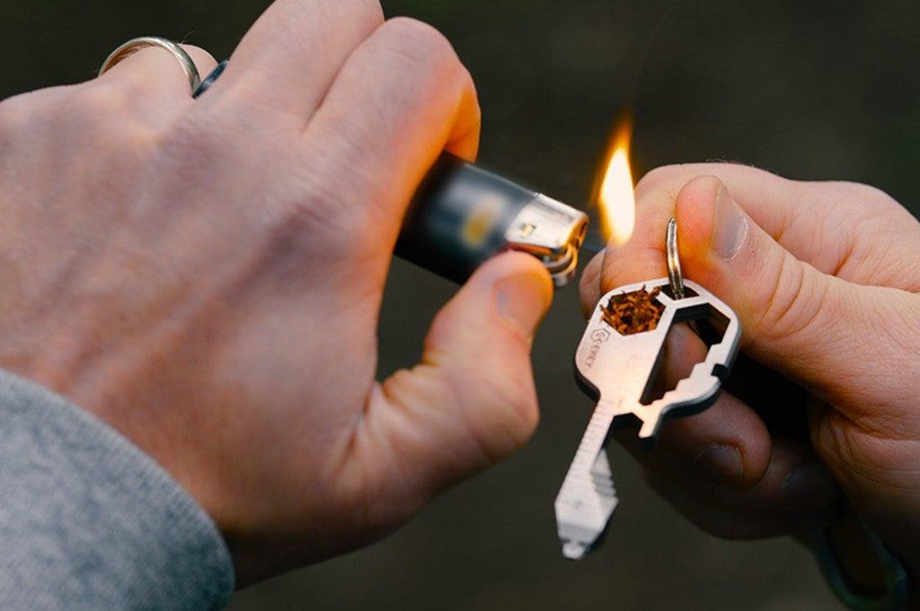 a man ignites a key shaped multitool