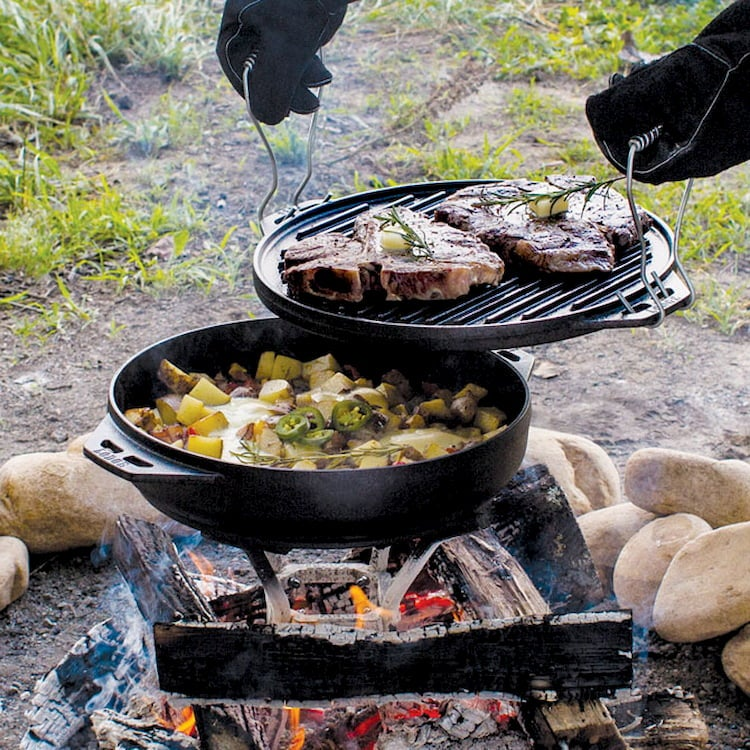 a cooking pot and grill over a campfire outdoors