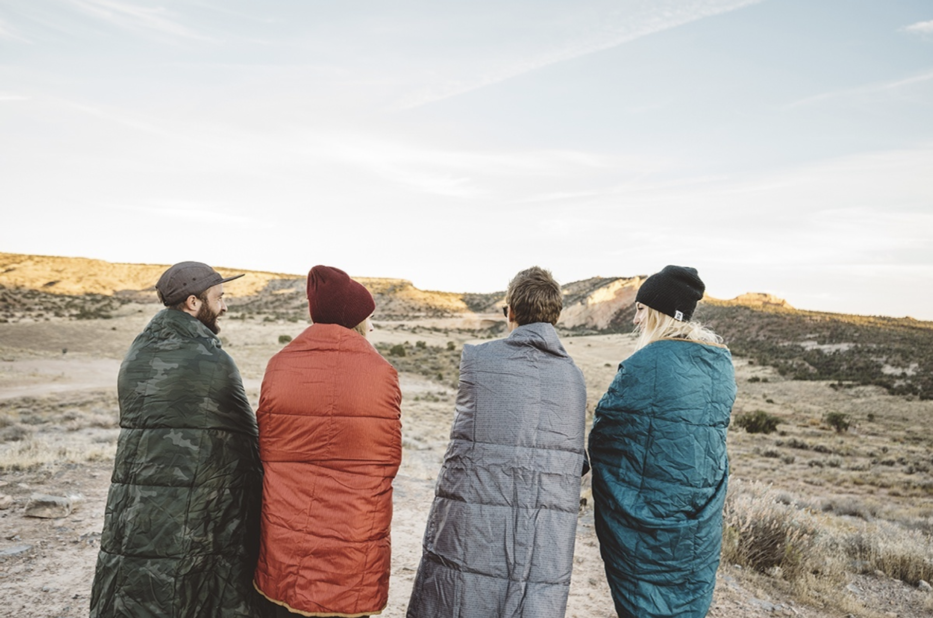 Four friends wrapped in the Kelty Bestie Blanket in the desert.