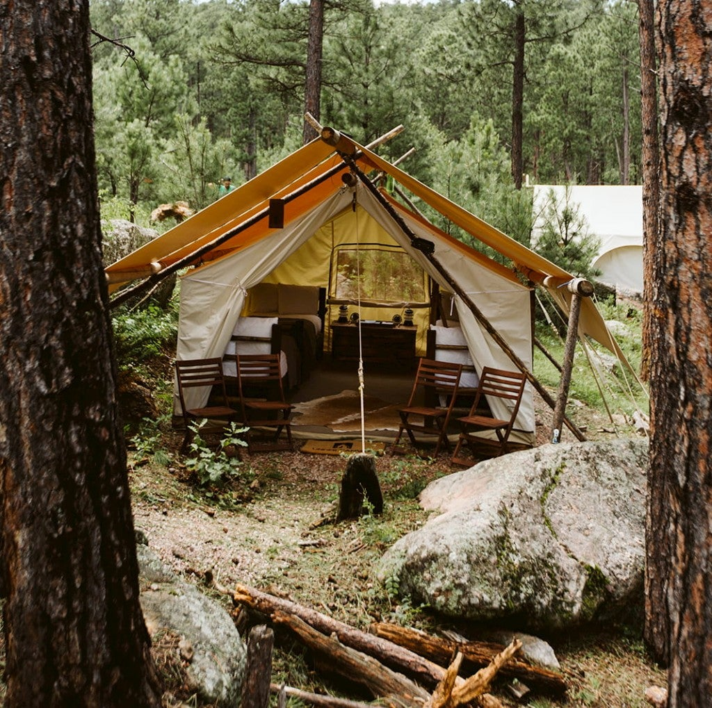 a glamping tent with a table and bed inside in a rocky forest