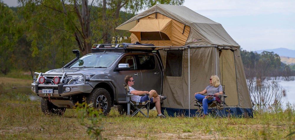 SUV with large tent and people sitting near lake