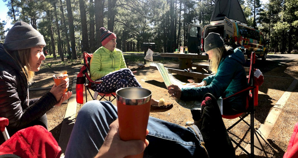 Group of friends drinking coffee at campsite.