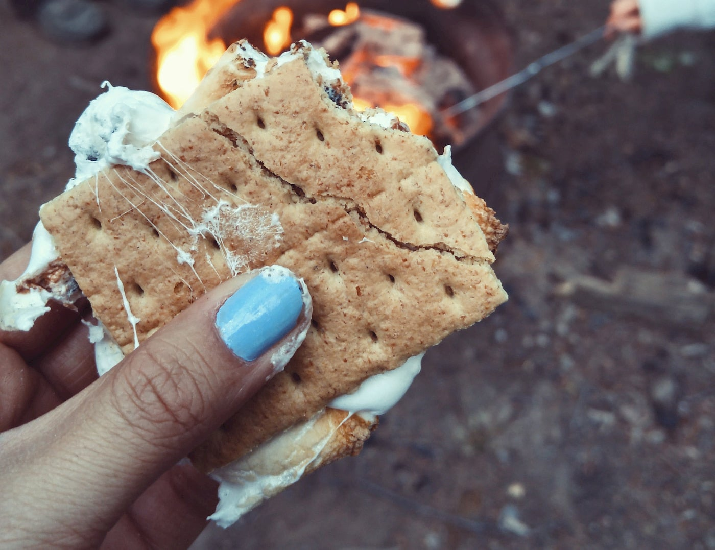 Women holding a s'more in front a a campfire.