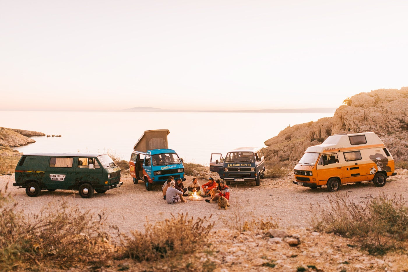 Group of camper vans parked on the edge of the coast at dusk.