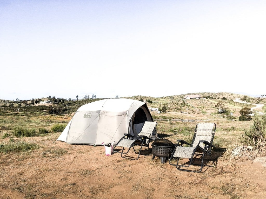 a scenic california countryside with a tent and two chairs