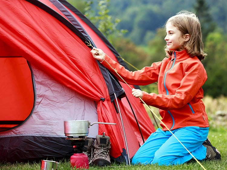 young girl setting up tent camp