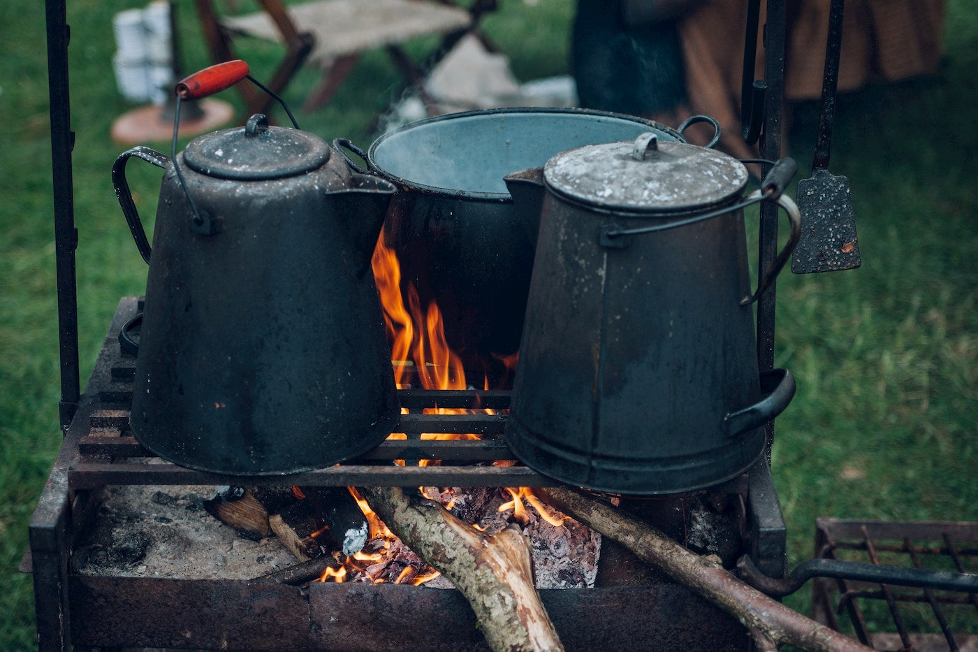 Kettles and pot cooking over a fire.