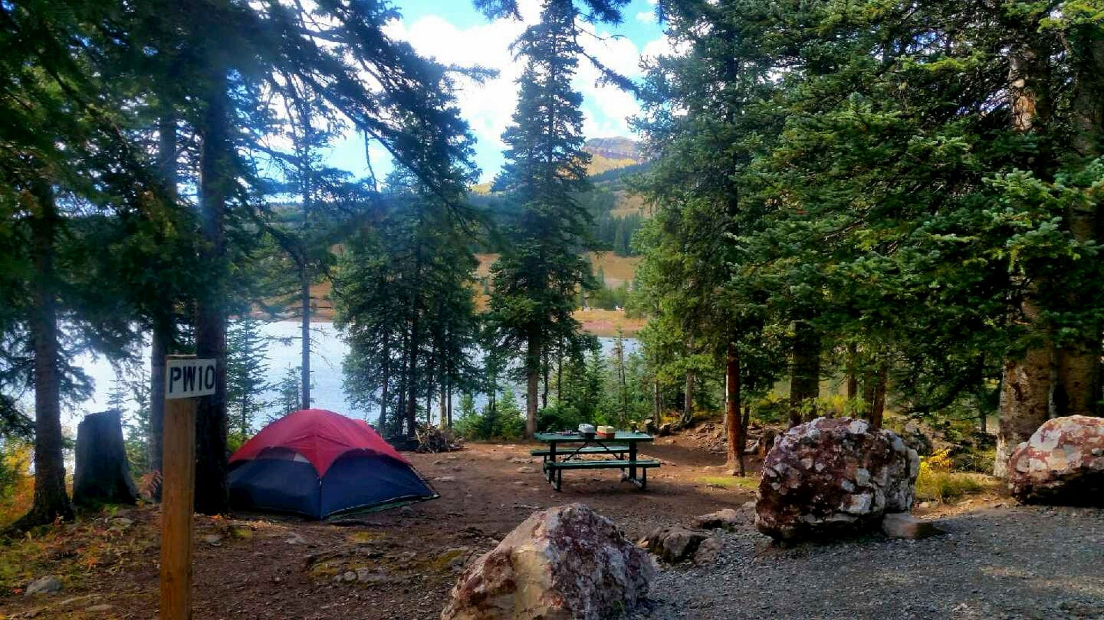 Lakeside campsite with tent and picnic table.