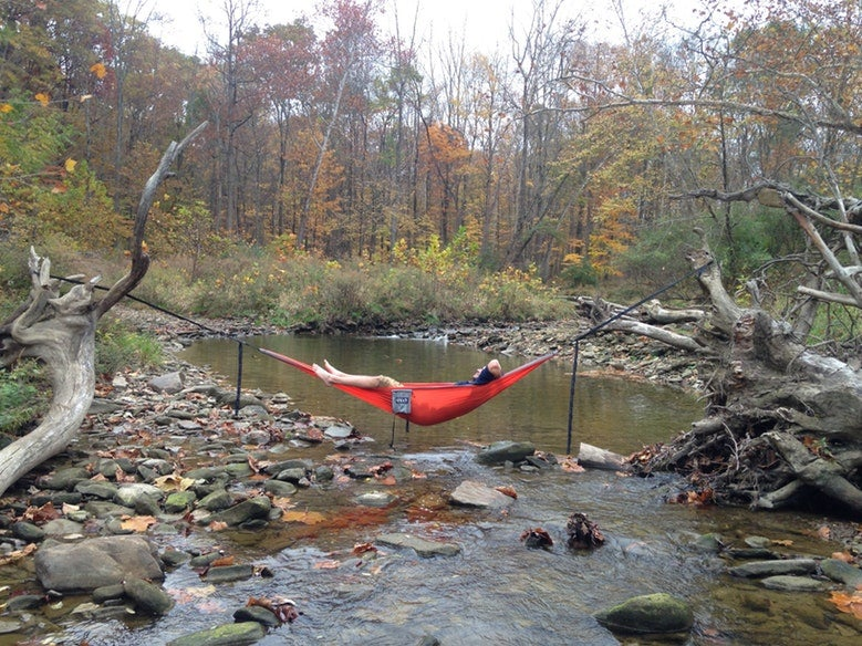 man lounges in red hammock over Cuyahoga Valley calm waters in the fall, photo from a camper on The Dyrt