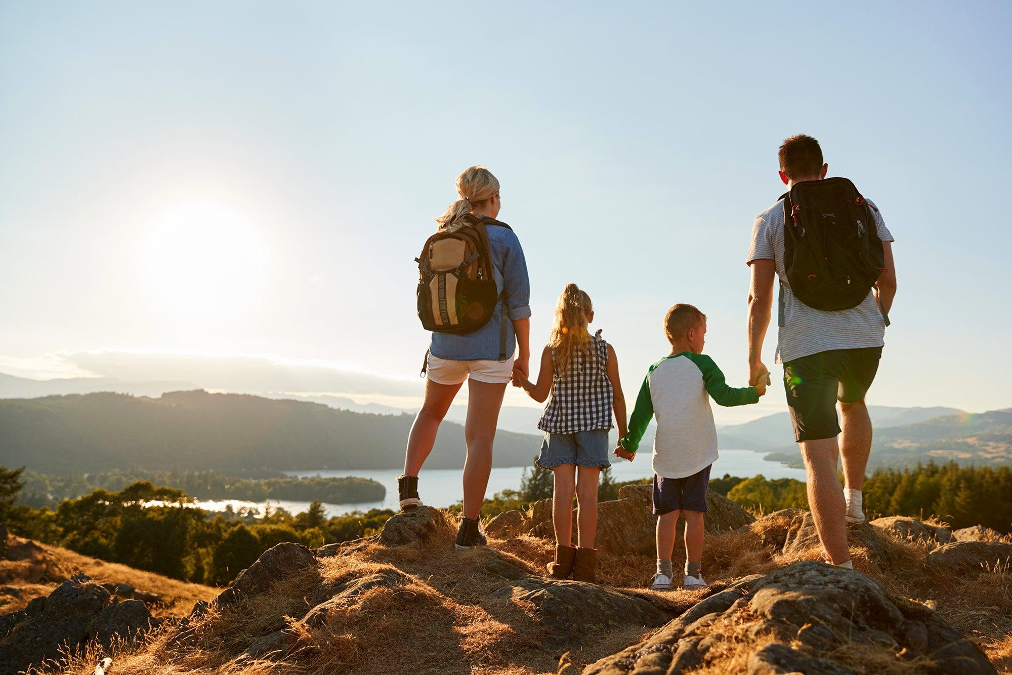 family hiking lake view at sunset