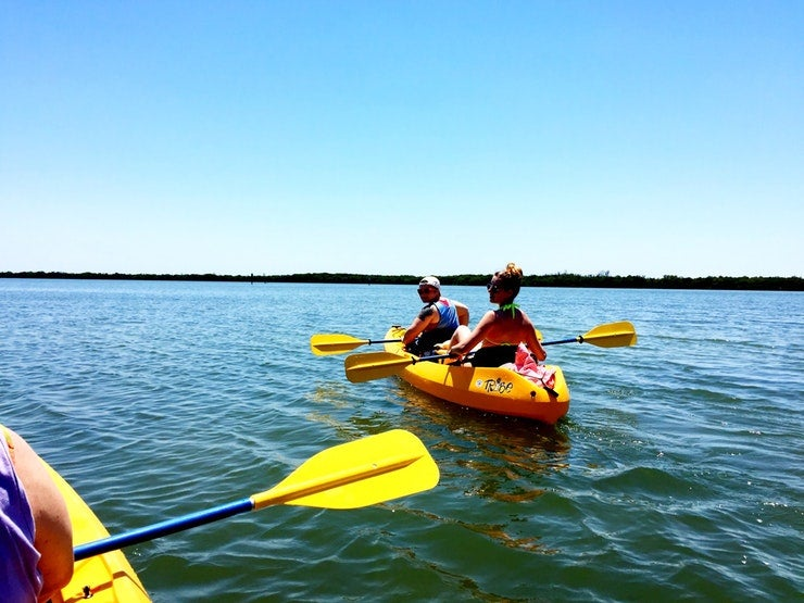 two kayakers in yellow boat look back at photographer on waters near Fort Desoto County Park, photo from a camper on The Dyrt