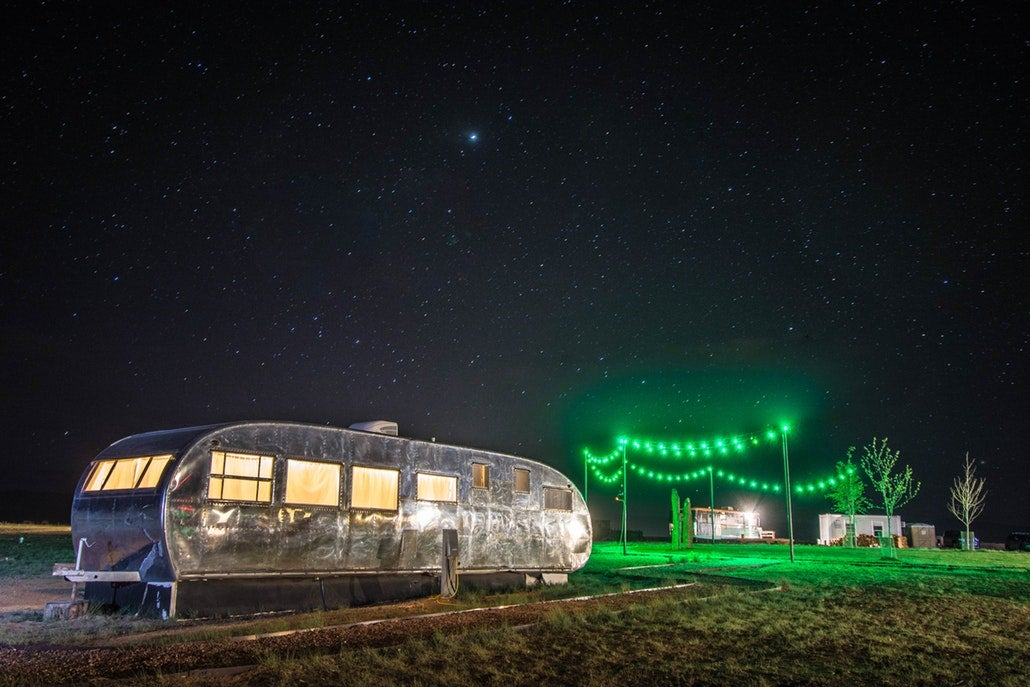 a camper trailer next to green lights