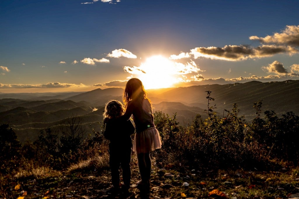 Kids watching the sunset from a mountain.