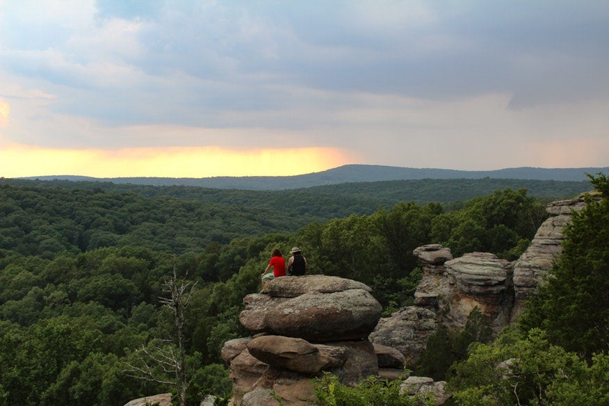 two hikers rest on boulder overlooking Illinois' Garden of the Gods at sunset, photo from a camper on The Dyrt