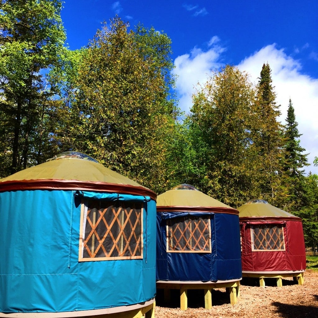 three bright colored yurts in the woods
