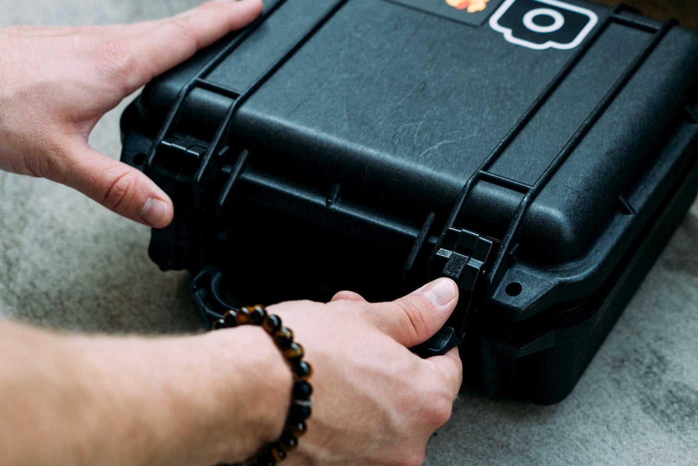Person opening a small pelican case.