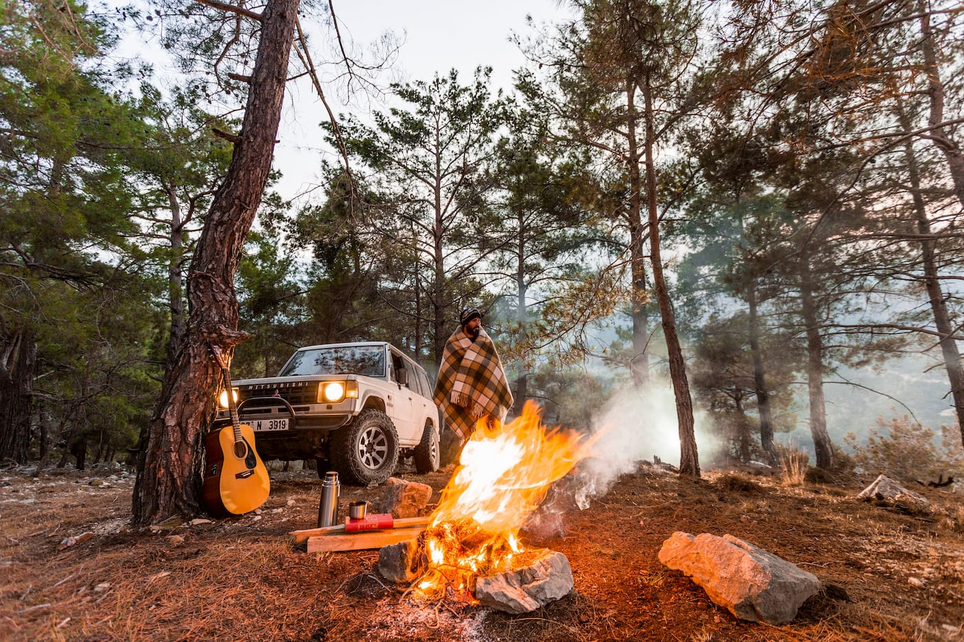 SUV parked in the woods beside a campfire.