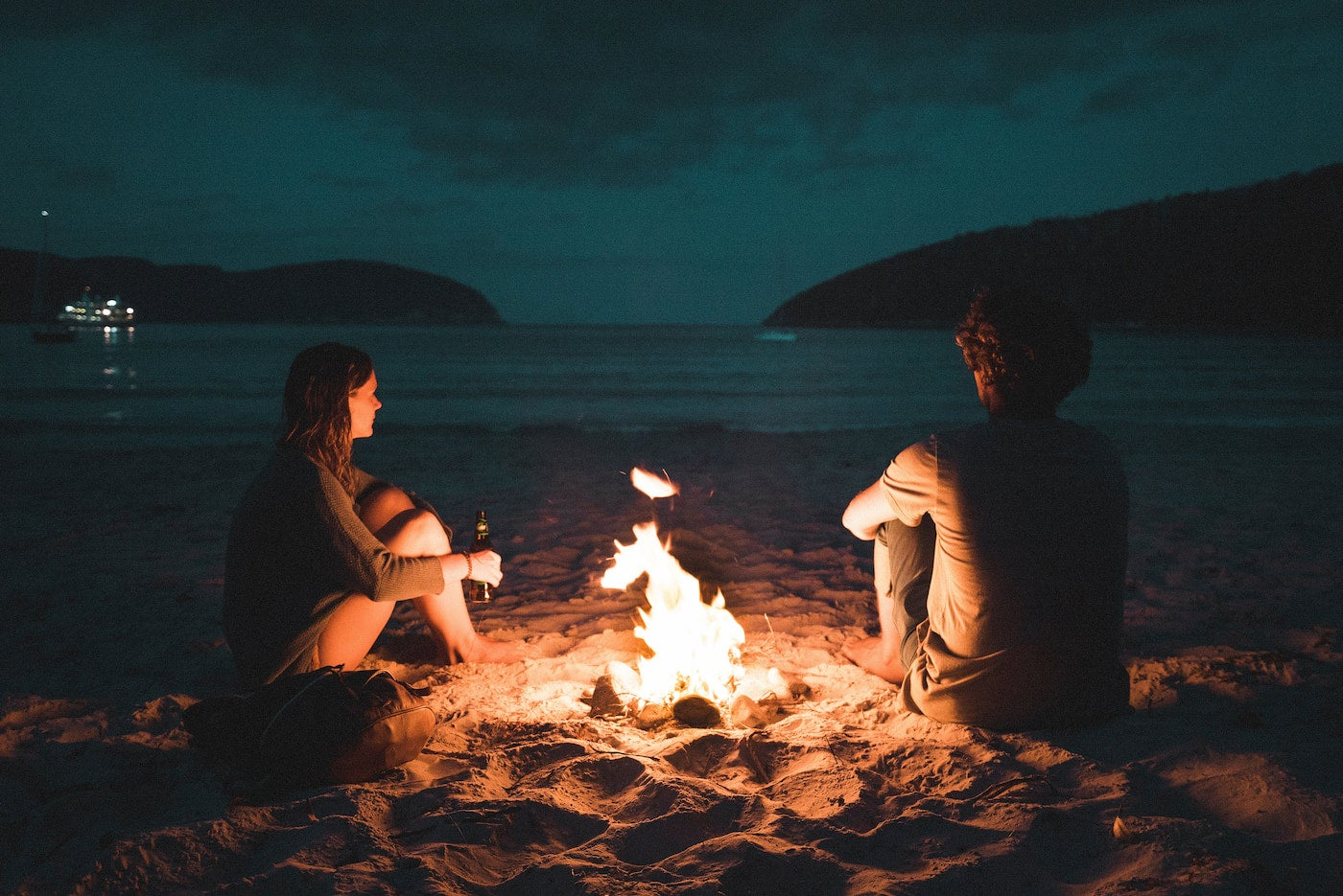 Two people talking and sitting around the campfire.