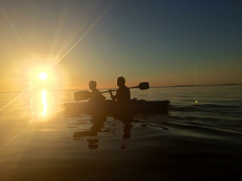 silhouette of kayakers on calm waters in Michigan's Wilderness State Park, photo from a camper on The Dyrt