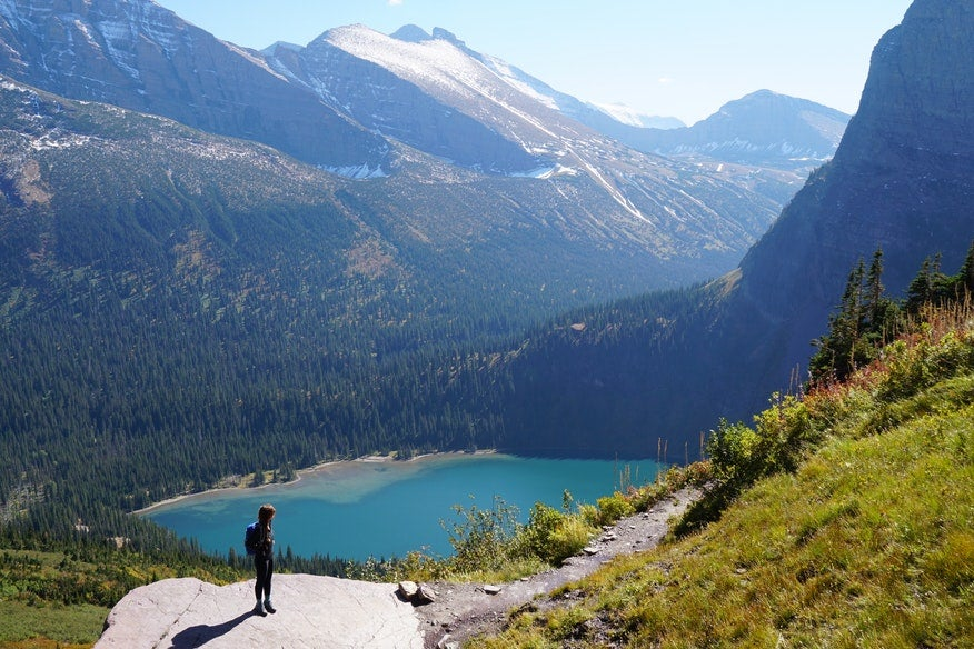 hiker stands on boulder overlooking lake near Many Glacier campground, photo from a camper on The Dyrt